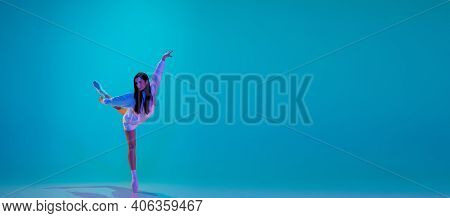 Young And Graceful Ballet Dancer Isolated On Blue Studio Background In Neon Light. Art, Motion, Acti