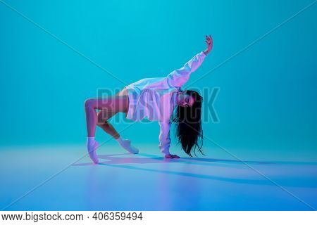 Dance. Young And Graceful Ballet Dancer Isolated On Blue Studio Background In Neon Light. Art, Motio