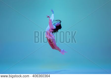 Flying High. Young And Graceful Ballet Dancer Isolated On Blue Studio Background In Neon Light. Art,