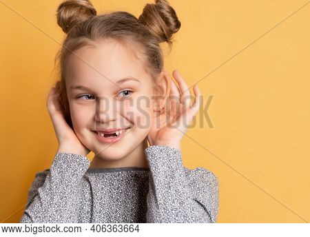 Close Up Of A Little Cheerful Smiling Girl Touches Her Ears And Looks Away On A Yellow Background. C
