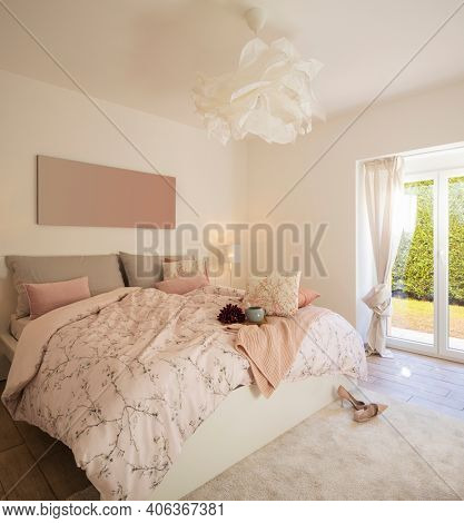 Modern, bright and luxury bedroom in design apartament. Fresh bed sheets and pillows above. There's a tray with a cup for breakfast.