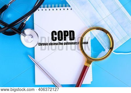 Copd Chronic Obstructive Pulmonary Disease, Text Written In A Notebook Lying On A Blue Background, W
