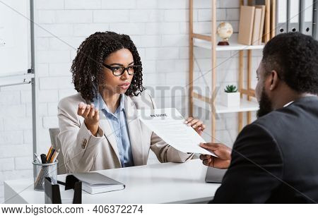 Serious Personnel Manager Taking Resume From Young Job Applicant On Work Interview At Modern Company