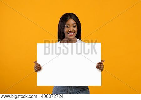 Smiling Young Black Woman Holding Blank Board For Advertisement Or Text On Yellow Studio Background.