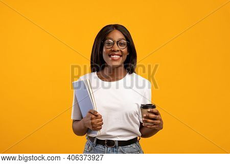 Positive Young Black Lady In Glasses Student Holding Notebooks And Coffee To Go, Having Break While