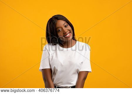 Cute Cheerful Black Young Lady In White T-shirt Posing On Yellow Studio Background, Copy Space. Beau