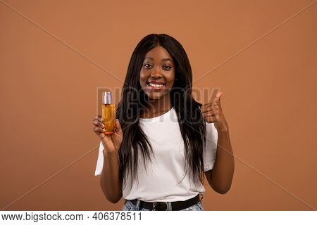 Pretty Young Black Woman With Long Beautiful Hair Holding Bottle With Hair Product, Serum Or Oil, Be
