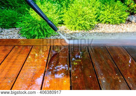 Cleaning Terrace With A Power Washer - High Water Pressure Cleaner On Wooden Terrace Surface