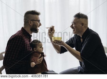 Male Gay Couple With Adopted Baby Girl At Home - Two Handsome Dads Feed The Baby Girl On Kitchen - M