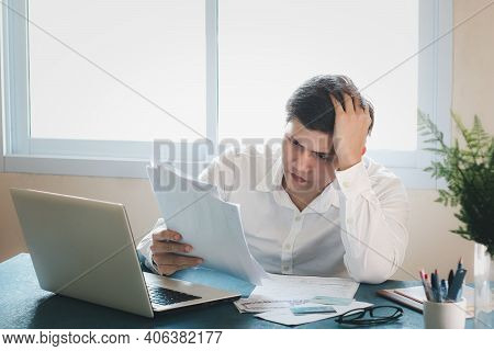 Young Asian Men Are Stressed Out In Business Office. Looking At Expense Bill And The Other Hand On H