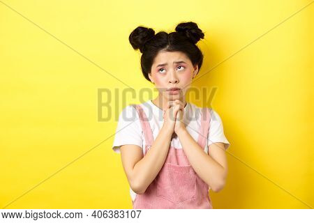 Sas Asian Girl Holding Hands In Pray, Pleading God, Looking Up And Begging, Standing On Yellow Backg