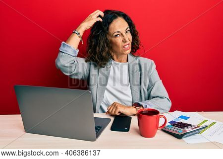 Beautiful middle age woman working at the office drinking a cup of coffee confuse and wondering about question. uncertain with doubt, thinking with hand on head. pensive concept.