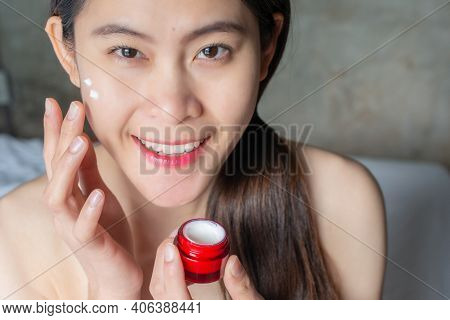 Portrait Of Young Asian Woman Applying Acne Cream/moisturizer On Her Face For Enhance Her Skin Or So