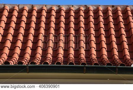 The Trough Of Two Roofs Bent Into A Turn With Italian Folded Tiles And A Metal Gutter. You Can See T