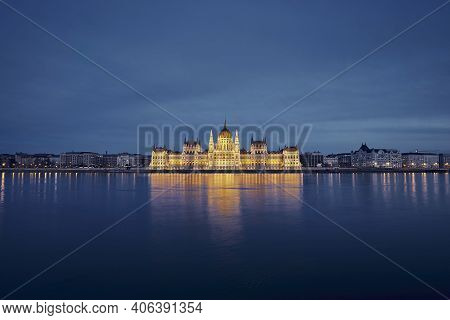 Reflection Of Illuminated Hungarian Parliament Building In Danube River. Budapest Skyline At Dusk, H