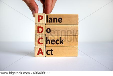 Pdca, Plan Do Check Act Symbol. Businessman Hand. Wooden Cubes And Blocks With Words 'pdca, Plan Do