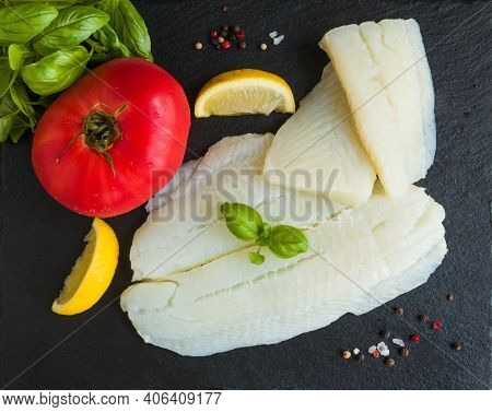 Raw Halibut Fish Fillet, Tomato, Lemon Basil And Spices On Black Stone Board, Top View