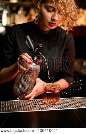 Close-up Of Woman Bartender At Bar Who Pouring Fizzy Liquid From Siphon Into Glass