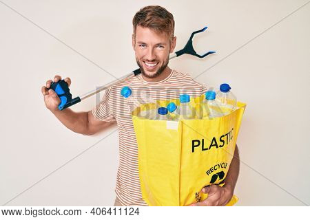 Young caucasian man holding recycling bag with plastic bottles and waste picker smiling and laughing hard out loud because funny crazy joke.