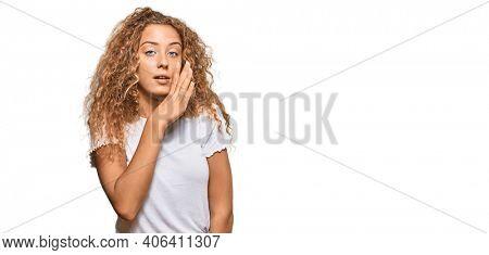 Beautiful caucasian teenager girl wearing casual white tshirt hand on mouth telling secret rumor, whispering malicious talk conversation