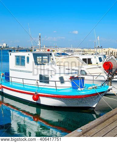White Motorboats Reflecting In Water, Wooden Pier, Marina Of Larnaca In Bright Sunshine Day, Cyprus