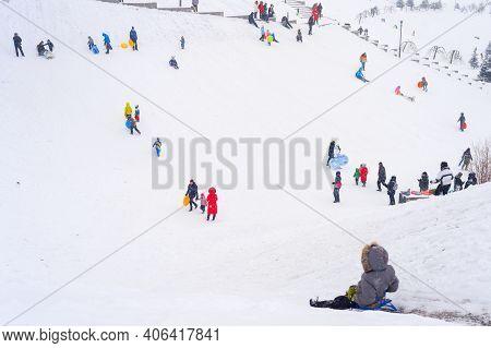Kiev, Ukraine - January 30, 2021: People Sledding From A High Hills In Kiev, Ukraine