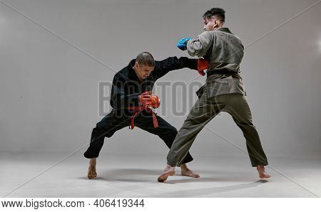 Fighting Guys During Mixed Fight Workout. Athletic Males In Kimono And Boxing Gloves Training Martia