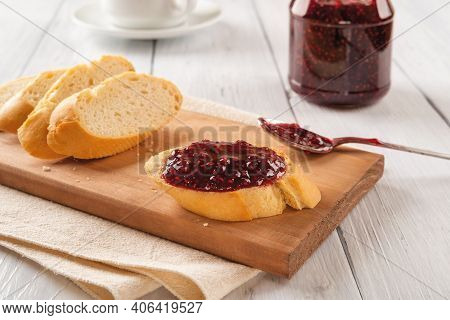 Tasty Sandwich With Raspberry Jam, Few Baguette Slices And Spoon On A Wood Cutting Board Against Jam