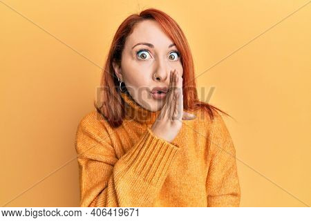 Beautiful redhead woman wearing casual winter sweater over yellow background hand on mouth telling secret rumor, whispering malicious talk conversation