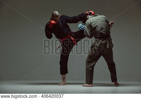 Sportive Males Fighting, Wearing Kimono And Boxing Gloves On Gray Studio Backdrop With Copy Space, M
