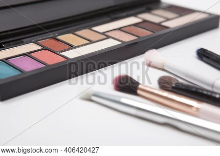 Eyeshadow Makeup Brushes Near Colorful Eyeshadow Palette Isolated