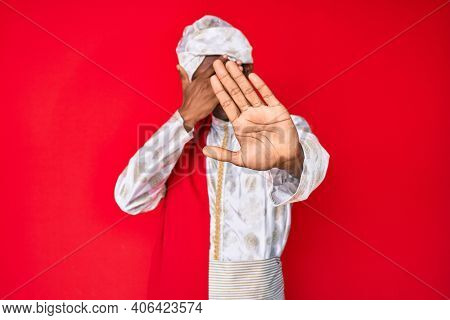 Handsome indian man wearing tradition sherwani saree clothes covering eyes with hands and doing stop gesture with sad and fear expression. embarrassed and negative concept.