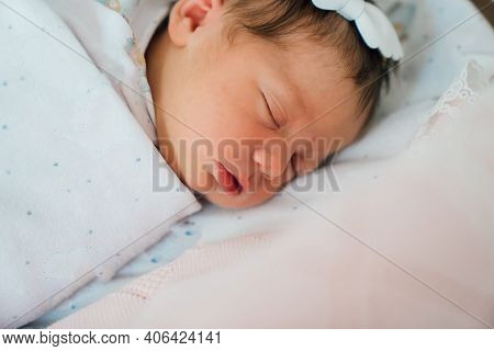 A Newborn Girl With A White Band On Her Head Sleeps In A Hospital Cradle.