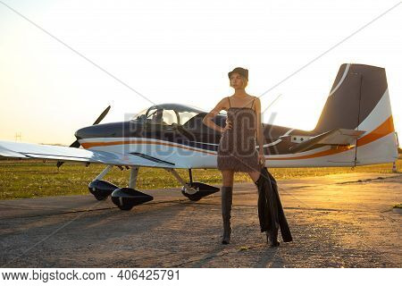 Beautiful Woman In Gray Dress Standing In Front Of Small Aircraft In Front Of Sunset.