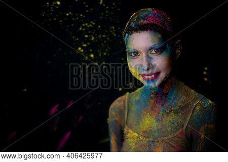 Portrait Of Beauty Model With Holi Colorful Powder Art Makeup On Black Studio Background.