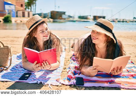 Two plus size overweight sisters twins women happy relaxing reading a book at the beach on summer holidays