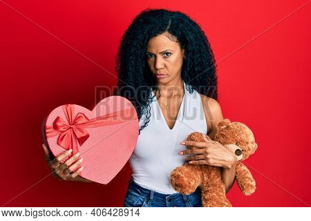 Middle age african american woman holding valentine gift skeptic and nervous, frowning upset because of problem. negative person.