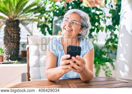 Middle age woman with grey hair smiling happy relaxing sitting at the terrace at home using smartphone