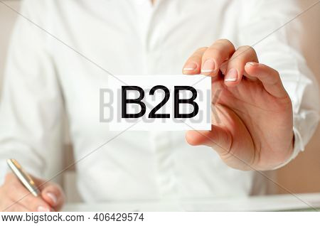 A Woman In A White Shirt Holds A Piece Of Paper With The Text: B2b. Business Concept For Companies.