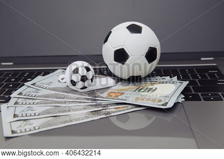 Soccer Whistle And Ball With Dollar Banknotes On Laptop. Betting On Sport Online Concept