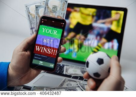 Smartphone With Betting Mobile Application And Males Hand With Soccer Ball. Sport And Betting Concep