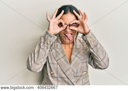 Young brunette woman wearing business jacket and glasses doing ok gesture like binoculars sticking tongue out, eyes looking through fingers. crazy expression.