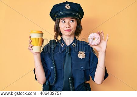 Young beautiful woman wearing police uniform holding donut and take away coffee smiling looking to the side and staring away thinking.
