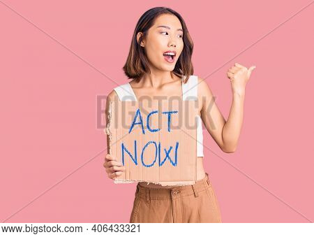 Young beautiful chinese girl holding act now banner pointing thumb up to the side smiling happy with open mouth
