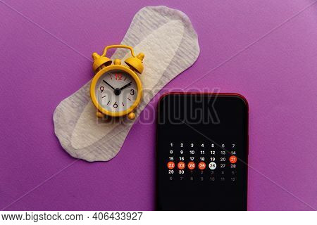 Menstruation Calendar In Smartphone With Sanitary Pad And Yellow Alarm Clock. Woman Critical Days, W