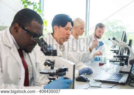Scientist And Students Working In Lab. Doctor Teaching Interns To Make Analyzing Research. Biotechno