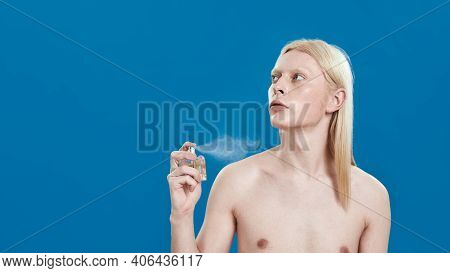 Young Caucasian Man With Long Fair Hair Spraying Fragrance On Naked Body While Standing On Blue Back