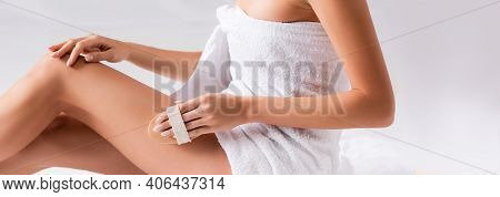Partial View Of Woman Wrapped In Towel Exfoliating Skin On Leg With Brush On White, Banner.