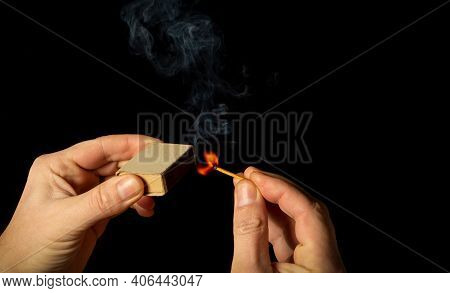 A Hand Holds Burning Match On Black Background. A Wooden Match Burns In The Hands Of Macro. Igniting