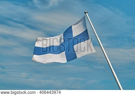Flag Of Finland Located In Front Of The Blue Sky. The Flag Flutters In The Wind. Windy, Sunny And Cl